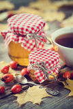 Jars of honey and tea cup. Maple leaves and dog rose berries. On rustic wooden table. Autumn still life. Selective focus Stock Photography