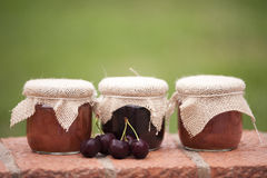 Jars of jam. Tree jars of jam and cherries Royalty Free Stock Photo