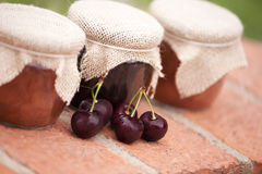 Jars of jam. Tree jars of jam and cherries outside Royalty Free Stock Photos