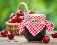 Jars of jam and basket with cherry. Stock Photo