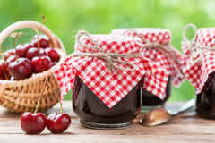 Jars of jam and basket with cherry. Stock Photography
