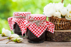 Jars of jam and basket of white roses Stock Images