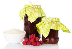 Jars of jam, bowl sugar and bunch ripe raspberry isolated. Jars of jam, a bowl of sugar and a bunch of ripe raspberry isolated on white background Royalty Free Stock Photography