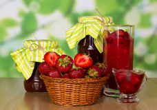 Jars of jam, strawberry in basket and glass with Royalty Free Stock Image