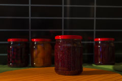 Jars with jam on the table. On black background Royalty Free Stock Images