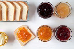 Jars of jam and toast. Food composition with jars of jam and toast on the stone table Royalty Free Stock Photography