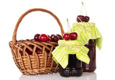Jars of jam, wicker basket with the sweet cherries Royalty Free Stock Images