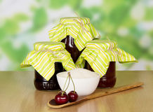 Jars of jam and wooden spoon Stock Image