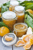 Jars with mandarine jam. Various jars with homemade mandarine jame on old wood table Stock Photo
