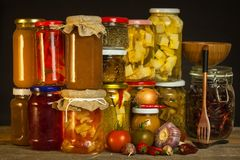 Jars with marinated food and organic raw vegetables. Preserved vegetables on wooden background. Various marinaded food. Life on a. Rural farm royalty free stock photography
