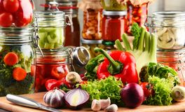 Jars with marinated food and raw vegetables on cutting board.  Royalty Free Stock Images