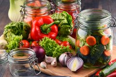 Jars with marinated food and raw vegetables on cutting board.  Royalty Free Stock Photo