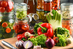 Jars with marinated food and raw vegetables on cutting board.  Stock Photography