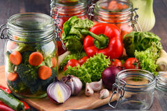 Jars with marinated food and raw vegetables on cutting board.  Stock Photo