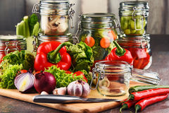 Jars with marinated food and raw vegetables on cutting board.  Royalty Free Stock Image