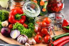 Jars with marinated food and raw vegetables on cutting board.  Stock Image