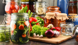 Jars with marinated food and raw vegetables on cutting board Royalty Free Stock Photography