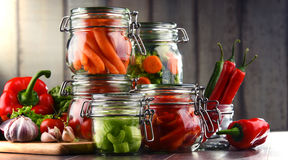 Jars with marinated food and raw vegetables on cutting board.  Stock Images