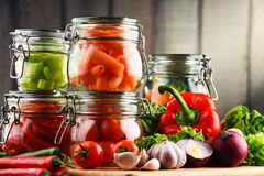 Jars with marinated food and raw vegetables on cutting board.  Royalty Free Stock Photography