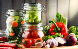 Jars with marinated food and raw vegetables on cutting board Stock Images
