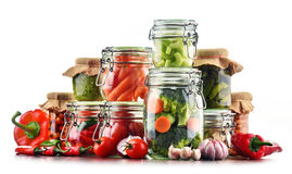 Jars with marinated food and raw vegetables isolated on white Stock Photo