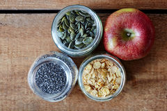 Jars with muesli and an red organic apple stock photos