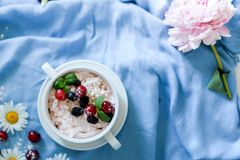 Jars of natural white yogurt with fruit salad with pink dragon fruit, berries and mint on table. Healthy eating. Copy space royalty free stock photo