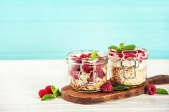 Jars with oat flakes and fresh berries. On wooden background Stock Photography