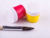 Jars with paint and brush. On white wooden background royalty free stock image