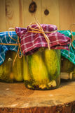 Jars pickled gherkins wooden table. Jars of pickled gherkins on a wooden table Royalty Free Stock Images