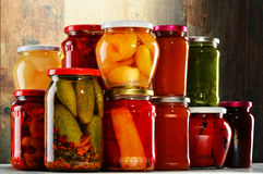 Jars with pickled vegetables, fruity compotes and jams  Stock Photo