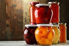 Jars with pickled vegetables, fruity compotes and jams royalty free stock photography
