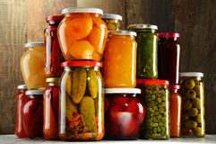 Jars with pickled vegetables, fruity compotes and jams Royalty Free Stock Photos