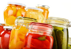 Jars with pickled vegetables, fruity compotes and jams isolated Stock Images