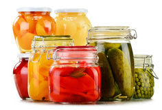 Jars with pickled vegetables, fruity compotes and jams Stock Photos