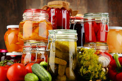 Jars with pickled vegetables and fruity compotes Royalty Free Stock Photos