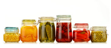 Jars with pickled vegetables and fruity compotes on white royalty free stock images