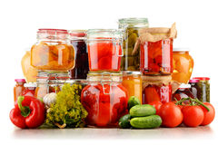 Jars with pickled vegetables and fruity compotes on white Stock Photography