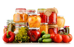Jars with pickled vegetables and fruity compotes on white Royalty Free Stock Photography