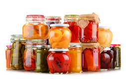 Jars with pickled vegetables and fruity compotes on white Stock Images