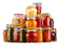 Jars with pickled vegetables and fruity compotes on white Stock Photos