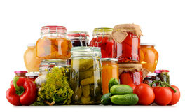 Jars with pickled vegetables and fruity compotes on white Royalty Free Stock Photos