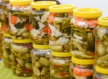 Jars of pickled vegetables for sale at Turkish bazaar. Jars with pickles, green tomatoes, pepper, cucumber, carrot. Jars of pickled vegetables for sale at Stock Images