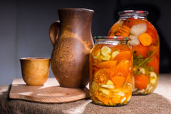 Jars of Pickles on Table with Wooden Handicrafts Royalty Free Stock Image