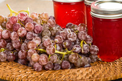 Jars of pink grape jelly with grapes Stock Photography