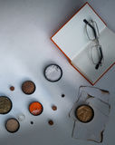 Jars of powders, book, glasses, sheets  charred paper on the table. top view Stock Image