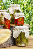 Jars of preserves on wooden table in the garden Stock Photography