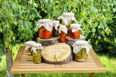 Jars of preserves on wooden table in the garden Stock Photos