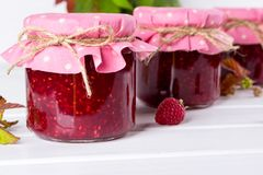 Jars with raspberry jam placed in rows and fresh raspberry. On white wooden table Stock Image