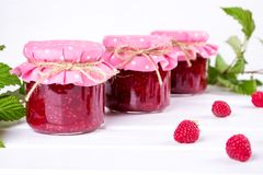 Jars with raspberry jam placed in rows and fresh raspberry. On white wooden table Stock Images